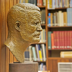 Scultped bust of a famous person, photograph set against a full bookcase