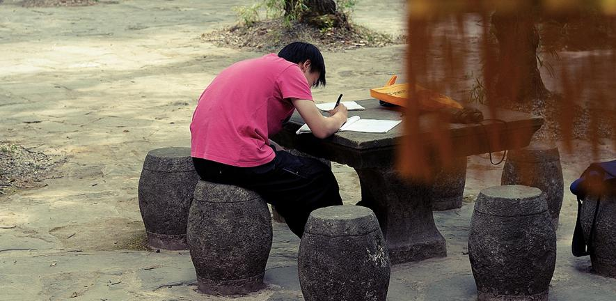 Person sitting and writing at a table in the Bamboo Temple in Kunming China