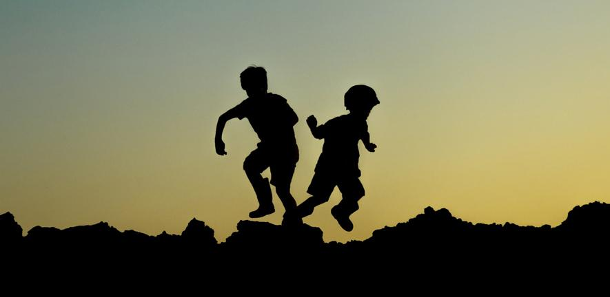 Photo silhoette of some young kids jumping against a sunset