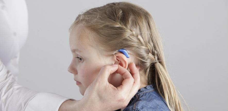 Photo of a young child having a hearing-aid fitted