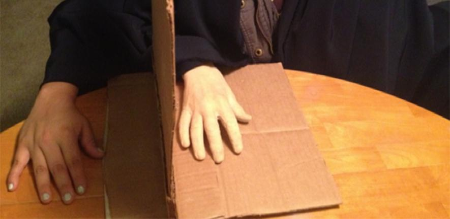 Photo of a person with a fake rubber hand resting it on a table