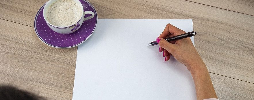 Photo of a hand holding a pen poised over an empty sheet of paper on a desk