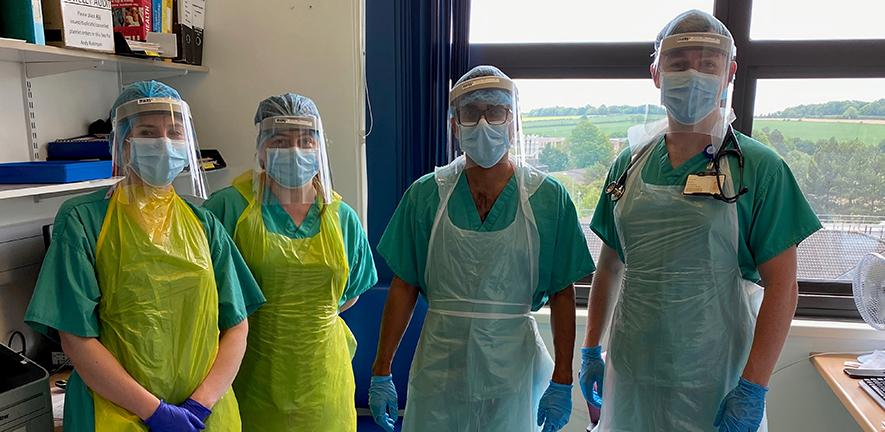 Photo of Professor Gupta and colleagues in full protective gear