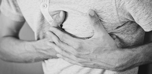 Black and white photo of a person clutching the left of their chest
